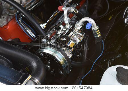 a chrome air conditioner compressor on a automobile.