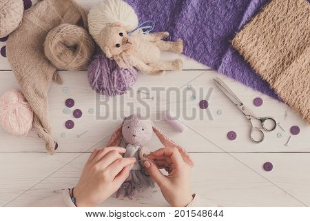 Process of making vintage toy, top view. Artisan pov, needlewoman hands sewing handmade rabbit, home workshop