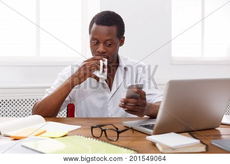 Young black employee at workplace. Checking social media on smartphone while coffee break