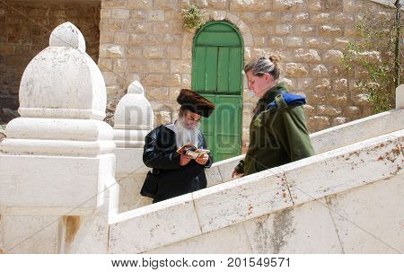 HEBRON ISRAEL - APRIL 12 2009: Orthodox jewish man and undefined israeli girl soldier next toTomb of the Patriarchs (Ma'arat HaMachpelah) in Hebron