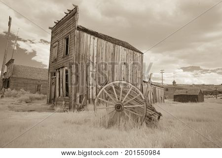 Wagon And Wooden Building In Bodie, California In Sepia