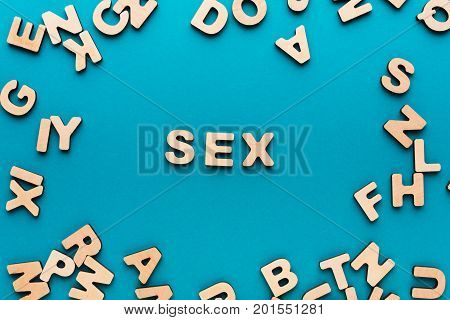 Word Sex in wooden letters frame on blue background. Couple relationship, satisfaction, romance concept