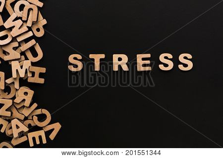 Word Stress on black background with pile of wooden letters. Depression, frustration, deadline concept