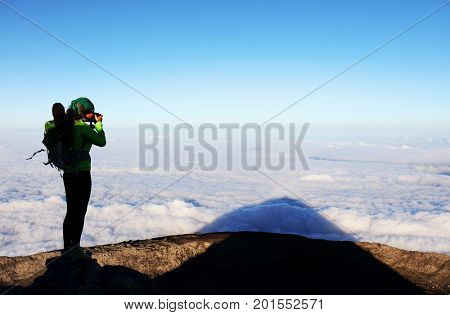 Young girl taking photos on Pico volcano (2531m), Pico Island, Azores, Portugal, Europe