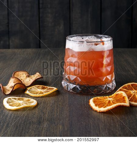 Cocktail on rustic wood background. Cold citrus alcohol beverage with tequila, blood orange juice and ginger beer, served with citrons and ice, copy space