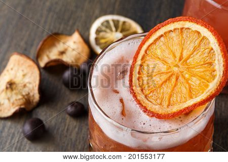 Cool alcohol cocktail at wooden background. Blood orange margarita with tequila on rustic table with citrons and chocolate snacks, closeup
