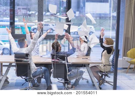 Group of young business people throwing documents and looking happy while celebrating success at their working places in startup office