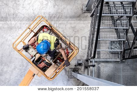 Aerial of a worker with blue hardhat on a cherry picker