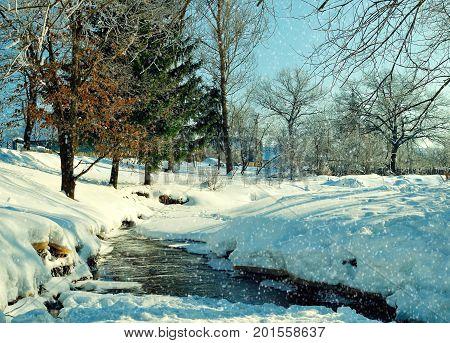 Winter rural landscape in sunny weather. Winter view of rural houses near the stream and winter snowdrifts on the foreground. Rural winter snowy scene. Winter rural landscape in sunny weather
