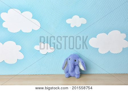 Cute knitted toy elephant on wooden table near blue wall with paper clouds