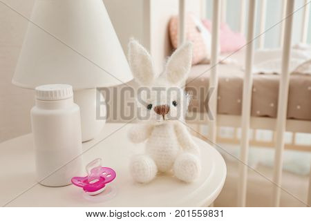 Baby toy, pacifier and body talc on table in light room