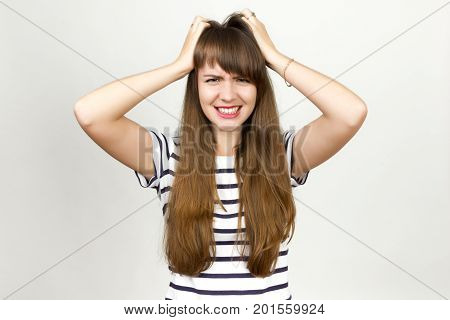 Portrait of upset the girl looks angry her hands in her hair she tearing her hair and screaming standing over gray background and looking at camera