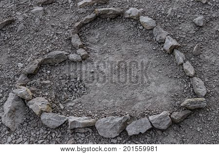 Heart is lined with stone on the ground. Close-up.