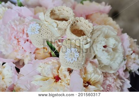 White baby booties on the flowers background