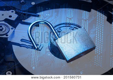 Opened padlock on computer motherboard and hard disk drive. Internet data privacy information security concept. Blue toned image.