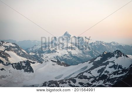 View of the surrounding Elbrus mountains from a height of 3800m at sunset. Photo from the slope of the Elbrus volcano