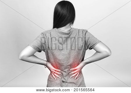 Pretty woman suffers from backache standing over gray background black and white with red accent