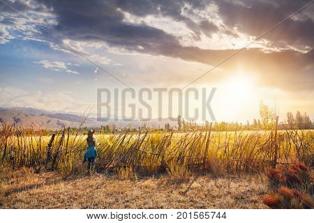 Woman In Hat On The Field At Sunset