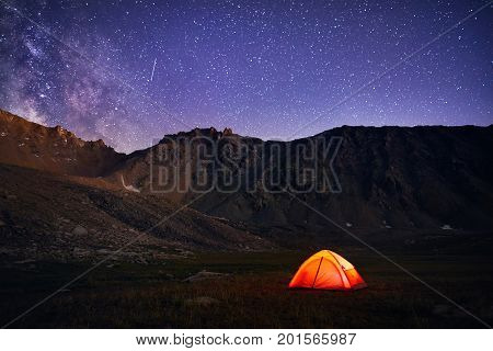 Orange Tent Glows Under Night Sky