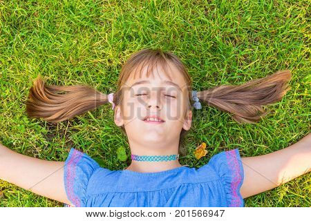 cute little girl with pigtails lies with her eyes closed on a green lawn