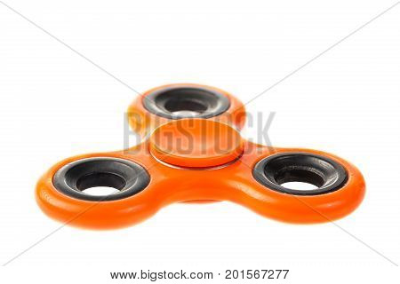 Orange fidget spinner close up stress relieving toy isolated on white background