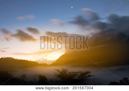 The moon is up during sunset View high mountain and sea fog at viewpoint Thailand