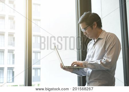 Casual Businessman / Office Worker With Glasses Looking At Laptop Screen And Typing In Front Of Offi