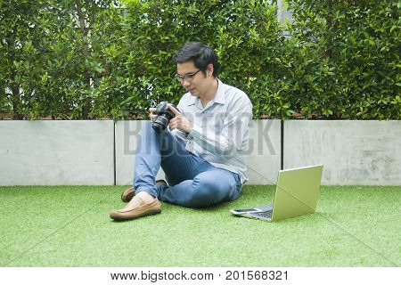 Asian Man In Casual Looking At Camera With Laptop And Smart Phone Sitting On Green Grass, Relaxing L