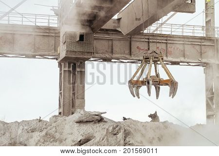 Overhead crane with mechanical multivalve clamshell grab in hot outdoors industrial plant shop. Heavy industry.