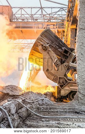 Pouring the hot melt from the ladle on transporter. Heavy metellyrgical industry.