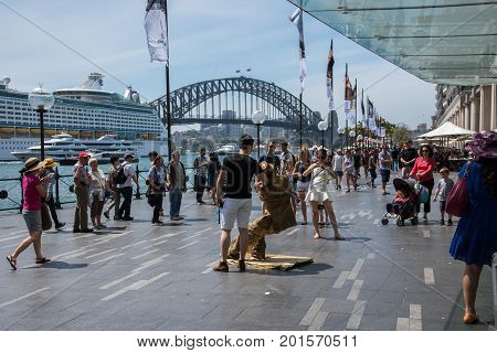 SYDNEY,NSW,AUSTRALIA-NOVEMBER 20,2016: Street busker with spectators and tourists on the Circular Quay waterfront with Harbour Bridge arch and cruise ship in Sydney, Australia.
