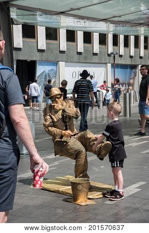 SYDNEY,NSW,AUSTRALIA-NOVEMBER 20,2016: Gold coloured street artist performing illusion at the Circular Quay with tourists in Sydney, Australia.