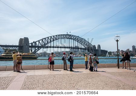 SYDNEY,NSW,AUSTRALIA-NOVEMBER 20,2016: Tourists taking pictures of the Sydney Harbour Bridge with ferry, sailboats, luna park and riverfront architecture in Sydney, Australia