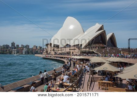 SYDNEY,NSW,AUSTRALIA-NOVEMBER 20,2016: Waterfront Opera Bar with crowds and the famous Sydney Opera House in Sydney, Australia