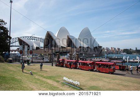 SYDNEY,NSW,AUSTRALIA-NOVEMBER 20,2016: Sydney Opera House, Harbour Bridge and Royal Botanic Garden touring train with tourists in Sydney, Australia.