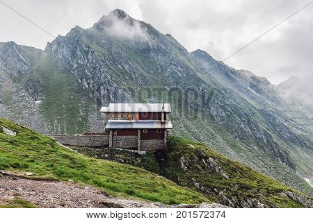 Mountain landscape house on the hill in high rocky Fagaras mountains at clouds in Carpathians Romania.