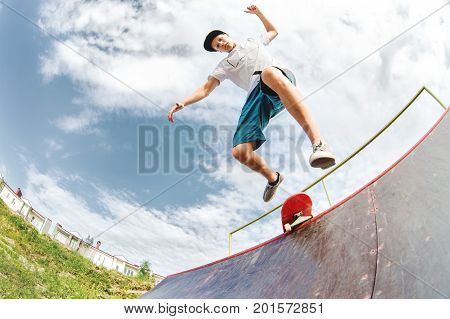 A young skater jumps from a ramp down when an unsuccessful attempt to do a trick in a skatepark