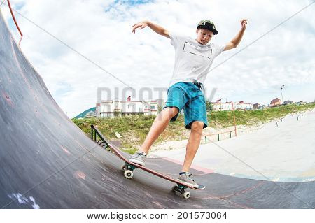 Young skater doing the trick over a ramp on a skateboard in a skate park. Wide angle