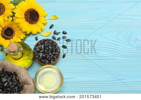 Sunflower oil in glass jug , seeds and flower on blue wooden background. top view with copy space