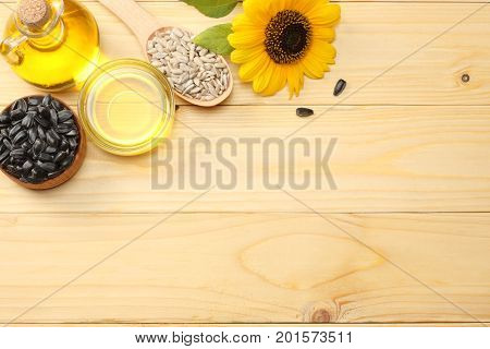 Sunflower oil in glass jug , seeds and flower on light wooden background. top view with copy space
