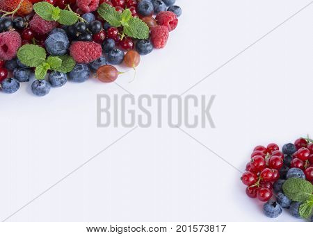 Various fresh summer berries on white background. Ripe raspberries strawberries blueberries gooseberries blackberries blackcurrants and red currants mint. Berries at border of image with copy space for text. Background berries. Top view.