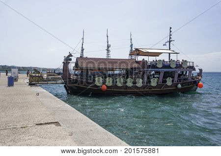 Thessaloniki, Greece - August 13 2017: Tourist ship moored by the waterfront. A ship with tourists, moored at Thermaikos gulf seafront before White Tower, the city landmark.