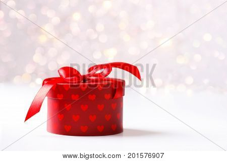 Holiday background red gift box with hearts and ribbon over festive bokeh background. Copy space card template