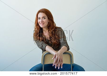 Portrait of young tender redhead woman with healthy freckled skin smiling on camera