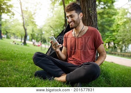 Attractive good-looking caucasian man looking with smile on the screen of his mobile phone, happy because of chatting with his girlfriend. Hipster casually weared sitting cross-legged on the grass under tree.