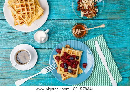 Homemade waffles with raspberries and blueberry, cup of coffee, milk and cutlery. Tasty breakfast