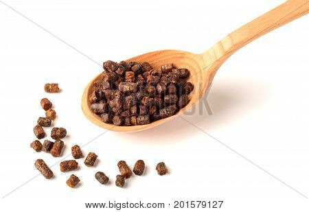 Granules of bee bread in a wooden spoon are isolated on a white background. Apitherapy. Beekeeping products. Strengthening immunity