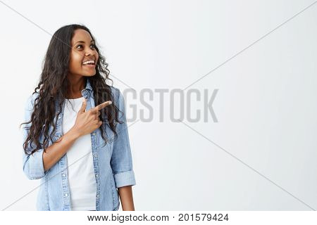 Horizontal studio shot of good-looking and cheerful Afro-american female wearing casual clothes keeping her index finger pointed at white blank wall with copy space for your text or advertising content