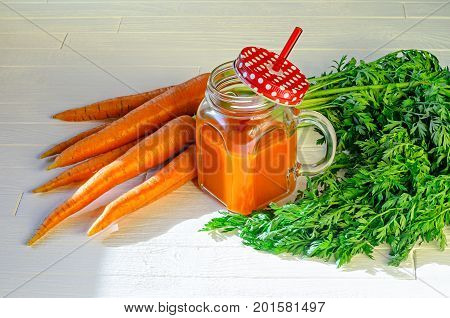 Healthy carrot smoothie in a jar with a red lid in a white polka dots and an orange straw and carrots on white wooden table top view. Healthy food background concept