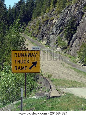 Runaway truck ramp in the forest on a mountain road, designed to slow down a vehicle and help prevent accidents if a commercial truck loses braking or loses control down a steep hill. poster
